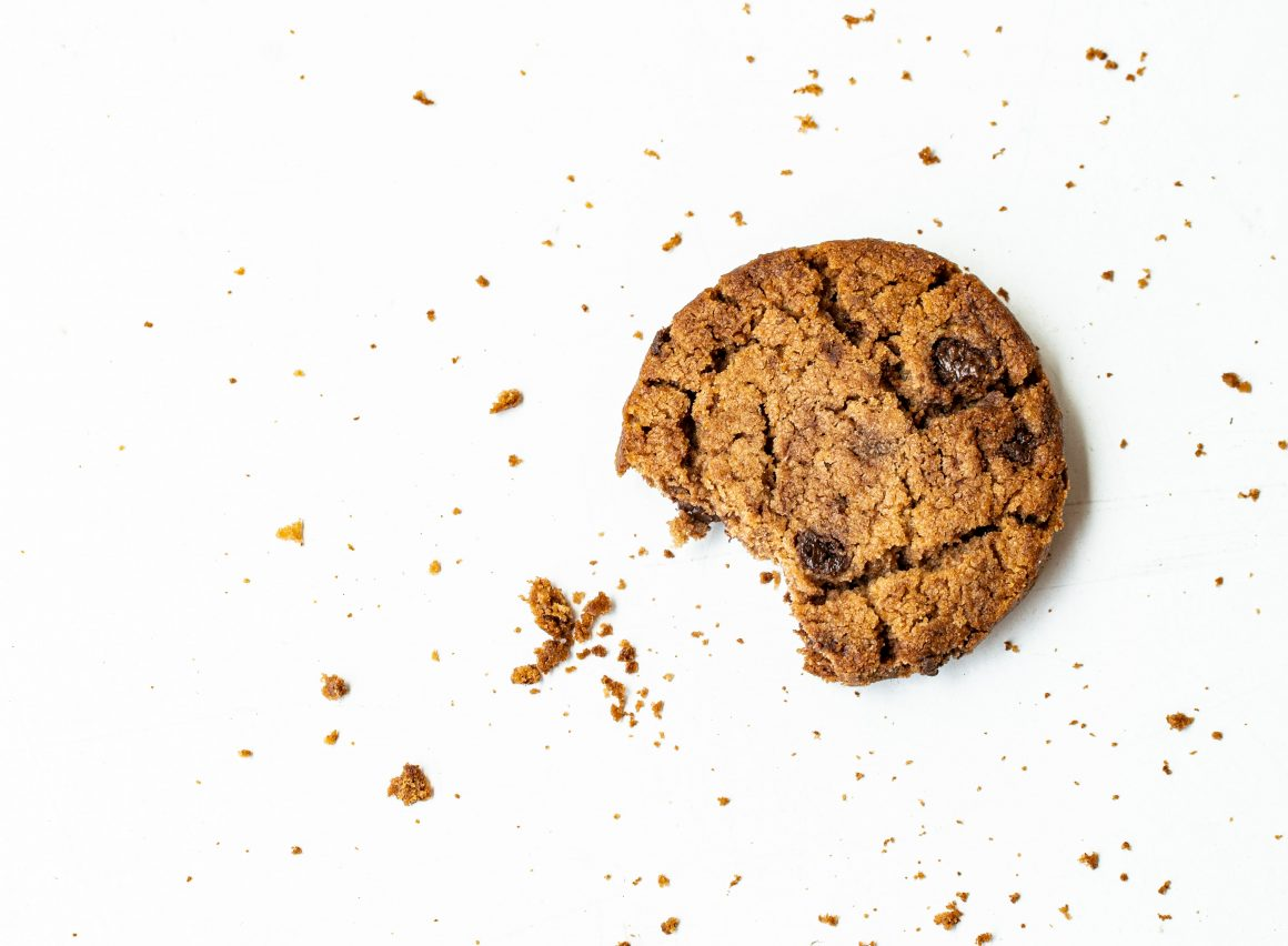 One chocolate chip cookie with crumbs surrounding it
